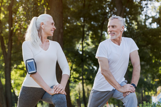 Low angle view of smiling senior couple doing warm up exercises while standing in park outdoors and looking on each other