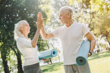 Mature couple standing with yoga carpet in hands in morning park before workout with high five each other
