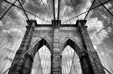 Scenic view of the architectural details of the Brooklyn Bridge in New York City in dramatic black and white monochrome under moody overcast skies
