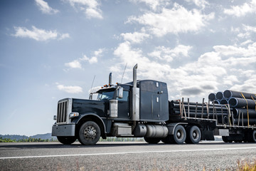 Black big rig semi truck transporting plastic pipes on step down semi trailer running on the road according to the given route Wall mural