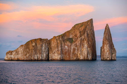 The volcanic rock formation of Kicker Rock (Leon Dormido) at sunset in the Pacific Ocean with sea birds silhouettes flying above the landmark, San Cristobal Island, Galapagos national park, Ecuador.