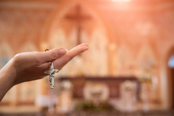 Woman hand holding rosary against cross and praying to God at church.