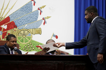 Haitian appointed Prime Minister Fritz William Michel  gives a folder to the president of the Parliament, Gary Bodeau, after his speech to present his general policy at the Parliament in Port-au-Prince