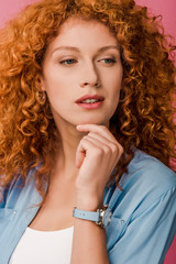 attractive thoughtful redhead woman isolated on pink
