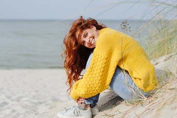 Smiling vivacious woman relaxing on a beach
