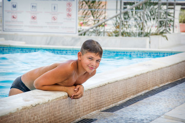 In the summer, a boy bathes in the pool.