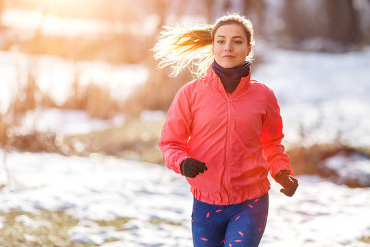 Young slim woman jogging in winter park