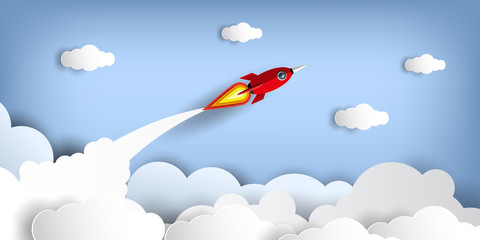 Paper art style of rocket flying over the sky while flying above a cloud.