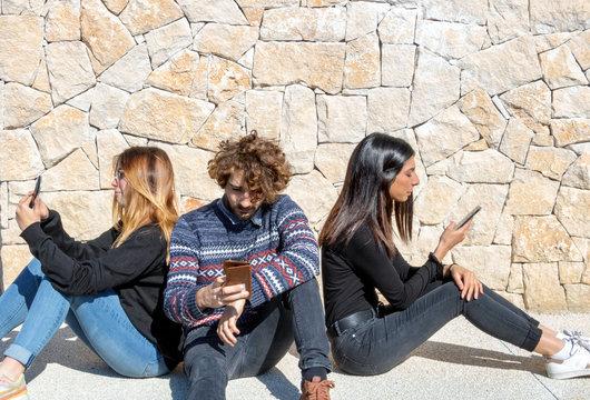 Groupe de jeunes assis en cercle et utilisant leur smartphone en se tournant le dos