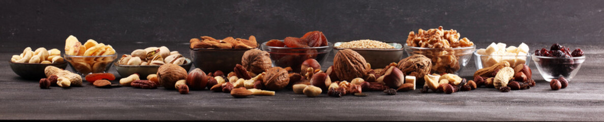 Composition with dried fruits and assorted healthy nuts on rustic background