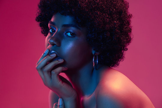 Summer's sunset. Portrait of female fashion model in neon light on gradient background. Beautiful african woman with trendy make-up and well-kept skin. Vivid style, beauty, cosmetics concept.