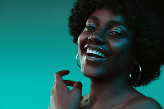 Deep ocean. Portrait of female fashion model in neon light on gradient background. Beautiful african woman with trendy make-up and well-kept skin. Vivid style, beauty, cosmetics concept.