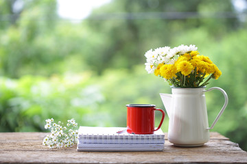 Red coffee mug with Chrysanthemum and daisy flowers and notebooks on wooden table at outdoor Wall mural