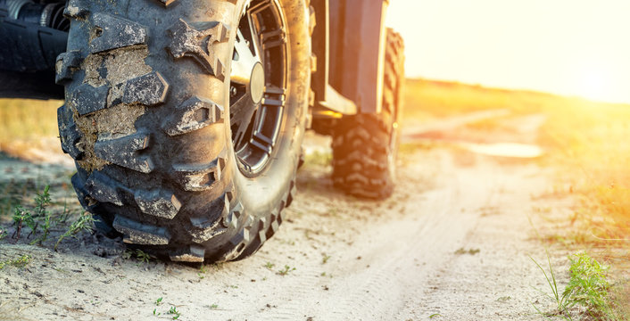 Close-up tail view of ATV quad bike on dirt country road at evening sunset time. Dirty wheel of AWD all-terrain vehicle. Travel and adventure concept.Copyspace.Toned