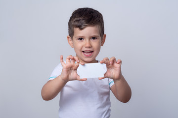Child showing empty blank paper, copy space. Kid holding bank card in hands. Universal template of a white bank or gift card. Ready to used in your design.