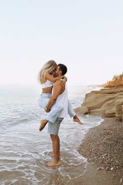 beautiful lovely couple wearing jeans,posing at summer beach