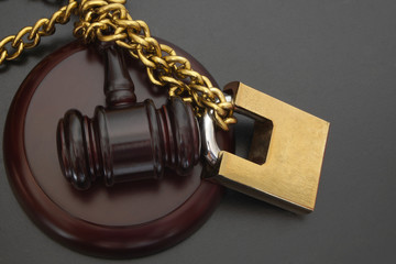 Non-independent justice, judge gavel locked with big padlock and chain