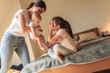 Mother playing with her daughter and baby boy in bedroom.They sitting on bed and making fun.