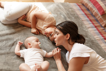 Mother playing with her daughter and baby boy in bedroom.Family concept.They lying on bed and making fun.