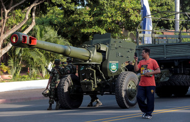 Man takes pictures during a military parade commemorating the army's founding in Managua