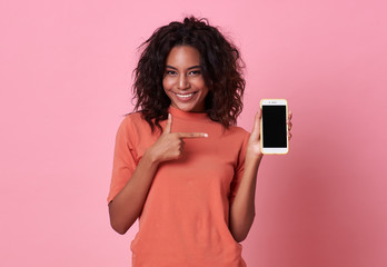 Portrait of a happy young african woman hand pointing at  blank screen mobile phone isolated over pink background. Wall mural