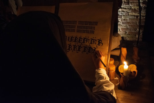 The hands of a medieval monk who write a manuscript by candlelight