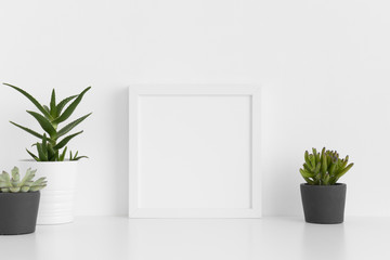 White square frame mockup with a various types of succulent plants on a white table.
