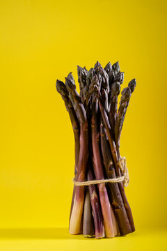 Bunch of fresh asparagus, food on yellow