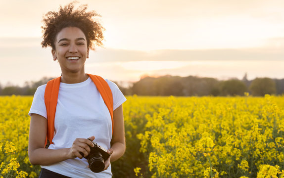 Mixed Race African American Girl Teenager With Camera in Yellow Flowers
