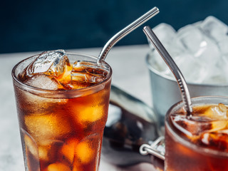 Cold brew coffee in a glass with metal straw on a dark background.Iced coffee