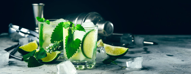 Cocktail Mojito with ice cube in a glass,slice lime, fresh leaf mint, shaker, jigger, metal straw, drops water on glass,Place for text,Banner