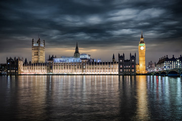 Fotomurales - Der Westminster Palast in London mit Regierungssitz und Parlament bei Nacht mit starker Bewölkung, Großbritannien