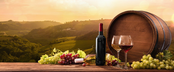 Photo sur Aluminium Alcool Wineglasses With Grapes And Barrel On A Sunny Background