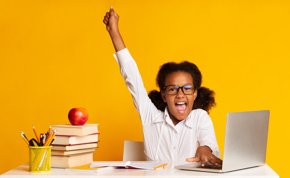 Afro Schoolgirl Raising Hand Sitting At Laptop In Studio