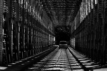 Fotobehang Brug Car riding on the road on the bridge immersed in light and shade. Black and white.