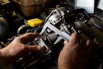 Hands measure the piston of a car engine using a ruler