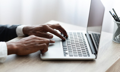 Unrecognizable african man typing at laptop in modern office