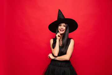 Young brunette woman in black hat and costume on red background. Attractive caucasian female model. Halloween, black friday, cyber monday, sales, autumn concept. Happy smiling. Fototapete