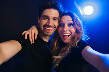 Pleased young loving couple having fun resting in a night disco club on concert take selfie by camera.