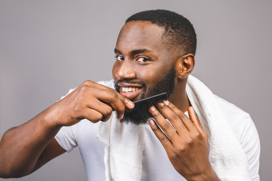 Portrait of handsome young african american black man combing his beard in bathroom. Isolated over grey background.