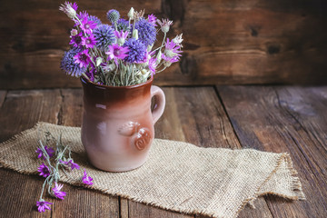 wildflowers in a clay pot on a wooden background.