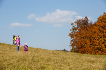 Mother with children hiking on a nice autumn day carrying kid