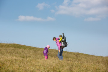 Mother with children hiking on a nice autumn day searching for wild herbs
