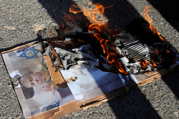 Pictures depicting Israeli PM Netanyahu are burnt by Palestinians during a protest against the planned visit of Netanyahu to the divided town of Hebron, in the Israeli-occupied West Bank