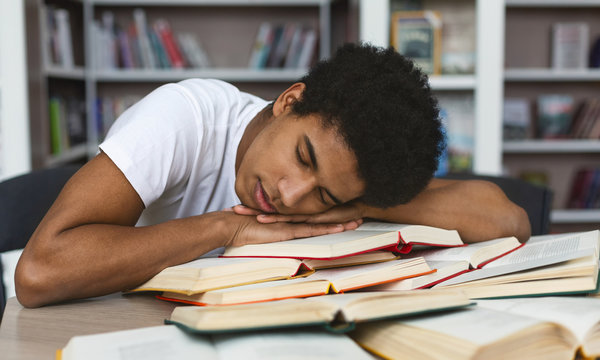 Exhausted afro guy sleeping on books in library