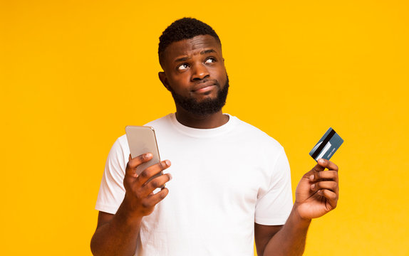 Doubtful african guy holding cellphone and credit card