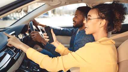 Afro couple driving car and using gps navigator