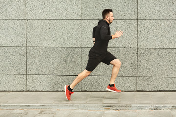 Male athlete running in city against grey wall