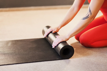 Side view slim young woman in a red suit turns off the black gymnastic mat after yoga or pilates. Concept of home workouts and fitness