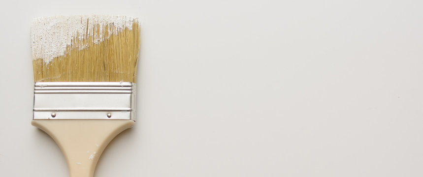 Paint brush stained with white paint, stucco on a white background. Horizontal shot. Close-up. The background is blurred. Concept - repair, wall plaster